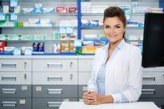 Schöner lächelnder Apotheker der jungen Frau, der seins Arbeit in der Apotheke tut Lizenzfreies Stockfoto