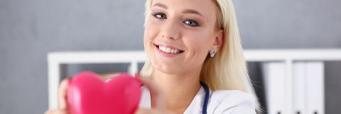 Schöner lächelnder blonder Ärztingriff Stockfotografie