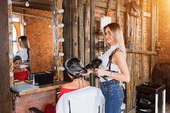 Schöner lächelnder blonder Friseur mit ihrem Kunden Sorgfalt, Beruf, Cosmetology Lizenzfreie Stockfotografie