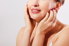 Schöner lächelnder Frauengesichtsabschluß oben Antialterskonzept Kollagen und plastische Chirurgie Frau, die ihr Gesicht berührt  Stockbilder