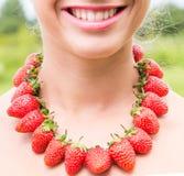 Schöner lächelnder Frauenhals mit den roten Perlen gemacht von der frischen Erdbeere Stockbild
