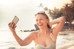 Schöner lächelnder Frauenreisender im Bikini auf dem Strand, der selfie bewegliches Foto am intelligenten Telefon während der Str stockfotografie