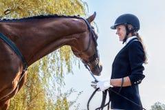 Schöner lächelnder Jockeymädchenstand nahe bei ihrem Pferd Stockfotos