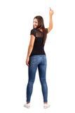 Schöner lächelnder junger Brunette, der mit Bleistift, hintere Ansicht zeigt Stockfotos