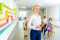 schöner lächelnder Lehrer, der in der Schule Korridor mit Kindern steht stockfotos
