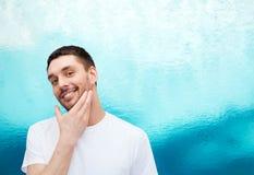 Schöner lächelnder Mann, der sein Gesicht berührt Stockfotografie