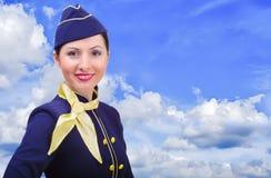 Schöner lächelnder Stewardess in der Uniform auf einem Hintergrundhimmel Lizenzfreie Stockfotos