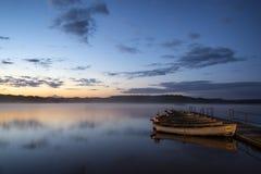 Schöner Landschaftssonnenaufgang über ruhigem See mit Booten auf Anlegestelle Stockbild