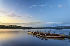 Schöner Landschaftssonnenaufgang über ruhigem See mit Booten auf Anlegestelle Stockfoto