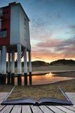 Schöner Landschaftssonnenaufgang-Stelzenleuchtturm auf dem Strand begrifflich Stockbild