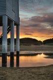 Schöner Landschaftssonnenaufgang-Stelzenleuchtturm auf Strand Stockfoto