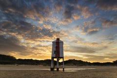 Schöner Landschaftssonnenaufgang-Stelzenleuchtturm auf Strand Stockfotos