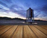 Schöner Landschaftssonnenaufgang-Stelzenleuchtturm auf Strand mit woode Lizenzfreie Stockfotografie