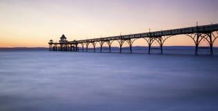 Schöner langer Belichtungssonnenuntergang über Ozean mit Pierschattenbild Stockfoto