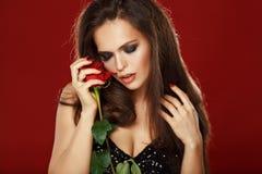 Schöner langhaariger Brunette, der eine rote Rose hält Studio, dunkel lizenzfreie stockfotos