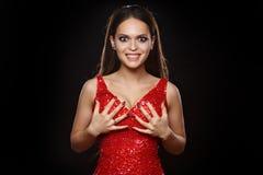 Schöner langhaariger Brunette in einem roten Kleid, das ihren Kasten hält stockfoto
