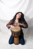 Schöner Latina, der eine Djembe Trommel (1) spielt Lizenzfreie Stockfotografie