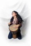 Schöner Latina, der eine Djembe Trommel (2) spielt Stockfotografie