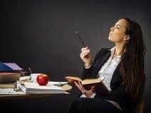 Schöner Lehrer, der an ihrem Schreibtischdenken sitzt Lizenzfreie Stockfotografie