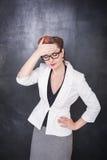 Schöner Lehrer mit Kopfschmerzen auf Tafelhintergrund stockfoto