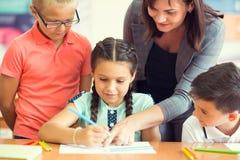 Schöner Lehrer Yong mit Gruppe klugen Kindern in der Schule lizenzfreie stockbilder