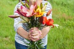 Schöner Lilienblumenstrauß, der durch eine Frau hält lizenzfreie stockfotos