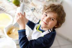 Schöner lustiger blonder Kleinkindjungen-Backschokoladekuchen und Probierenteig in der inländischen Küche Lizenzfreie Stockfotografie