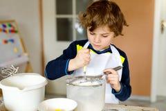 Schöner lustiger blonder Kleinkindjungen-Backschokoladekuchen und Probierenteig in der inländischen Küche Lizenzfreies Stockbild
