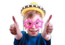 Schöner lustiger Junge in einem blauen T-Shirt, das buntes stilvolles sternförmiges und Gläser und gelber Sombrerohut trägt, zeigt Lizenzfreies Stockfoto