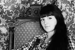 Schöner Mädchen Brunette im Sessel Lizenzfreie Stockfotos
