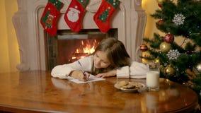 Schöner Mädchen-Schreibensbuchstabe mit 10-Jährigen zu Santa Claus mit Wünschen stock footage
