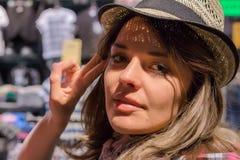 Schöner Mädchenabschluß herauf Portrait Frau im Shop versucht auf Kleidung Sie in einer guten Laune Lizenzfreie Stockbilder