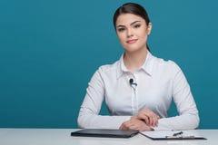 Schöner Mädchenfernsehnachrichtensprecher berichtet über das Sitzen Lizenzfreie Stockbilder