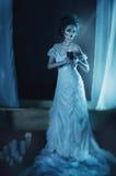 Schöner Mädchengeist, Hexenbraut in einem weißen Kleid, das eine schwarze brennende Kerze in den Händen hält Stockfotografie