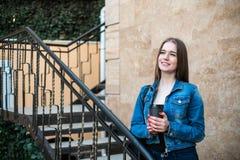 Schöner Mädchengetränkkaffee an der Treppe draußen lizenzfreies stockfoto