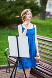 Schöner Mädchenkünstler auf der Straße in einem blauen Kleid, zeichnet auf das Gestell Stockbilder