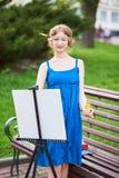 Schöner Mädchenkünstler auf der Straße in einem blauen Kleid, zeichnet auf das Gestell Lizenzfreie Stockfotografie