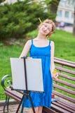 Schöner Mädchenkünstler auf der Straße in einem blauen Kleid, zeichnet auf das Gestell Lizenzfreie Stockbilder