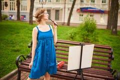 Schöner Mädchenkünstler auf der Straße in einem blauen Kleid, zeichnet auf das Gestell Stockfoto