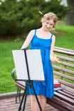 Schöner Mädchenkünstler auf der Straße in einem blauen Kleid, zeichnet auf das Gestell Stockbild