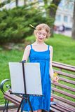 Schöner Mädchenkünstler auf der Straße in einem blauen Kleid, zeichnet auf das Gestell Lizenzfreies Stockfoto