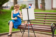 Schöner Mädchenkünstler auf der Straße in einem blauen Kleid, zeichnet auf das Gestell Lizenzfreie Stockfotos