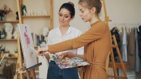 Schöner MädchenKunststudent spricht mit ihrem Lehrer, der Bild auf Gestell betrachtet und Bürste und Palette, Meister hält stock video footage