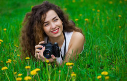Schöner Mädchenphotograph mit dem gelockten Haar, das eine Kamera hält und auf dem Gras liegt Stockbild