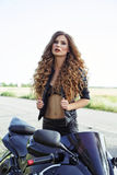 Schöner Mädchenradfahrer nahe einem Sportmotorrad stockbild
