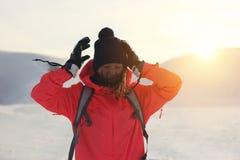 Schöner Mädchenreisender auf dem Wintergebiet kämpfend mit dem Wind Stockfoto