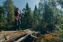 Schöner Mädchenstand auf Klotz und Kühlen nach Reise Frauenreisender im Sommer gibt Holzbrücke im Hintergrund von weiter lizenzfreies stockfoto