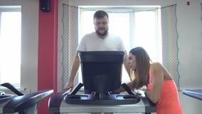 Schöner Mädchentrainer erklärt, wie man Übungen in der Turnhalle auf einer Tretmühle einen vollen Mann mit einem Bart antut, pers stock video