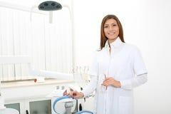 Schöner Mädchenzahnarzt nahe dem zahnmedizinischen Stuhl, der Sicherheit glas hält stockfotografie