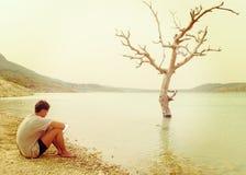 Schöner männlicher Hippie gesessen durch ruhigen See Stockbild
